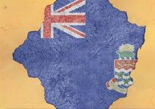 开曼群岛状态旗子打破的物质门面结构墙壁 免版税库存照片
