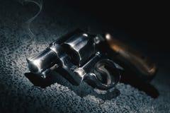 开枪与在地板上的烟,大反差图象 库存图片