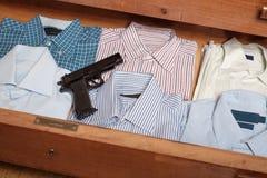 开枪在抽屉衬衣充分掩藏在家 库存图片