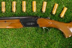 开枪在绿色草坪和很多弹药在它旁边作为背景 库存照片