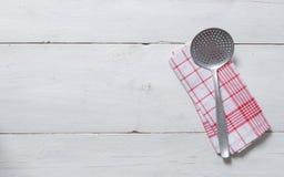 开槽的匙子和洗碗布在土气木背景 免版税库存图片