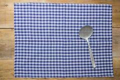 开槽的匙子和洗碗布在土气木背景 免版税图库摄影