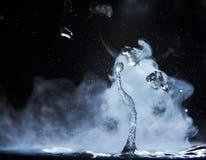 开水飞溅与蒸汽在黑背景特写镜头 免版税库存照片