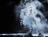 开水飞溅与蒸汽在黑背景特写镜头 免版税库存图片
