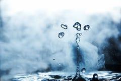 开水飞溅与蒸汽在黑背景特写镜头 免版税图库摄影
