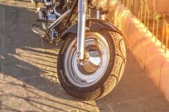 开汽车在有灼烧的太阳的城市街道上停放的自行车第一个轮子 免版税库存图片
