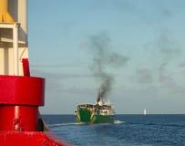 开汽车在海军部海湾,贝基亚岛外面的客船 库存图片