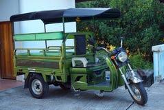 开汽车在街道上的出租汽车tuk-tuk,摩托车骑士,地方车为采取乘客 库存图片