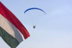 开汽车有深蓝天空和匈牙利旗子的滑翔伞 免版税图库摄影