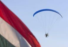 开汽车有深蓝天空和匈牙利旗子的滑翔伞 库存照片