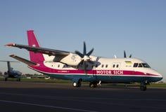 开汽车西奇航空公司运行在跑道的安-140航空器 免版税图库摄影