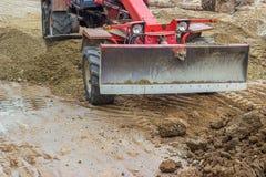开汽车运作在成水平的平地机石渣上在路 免版税库存照片