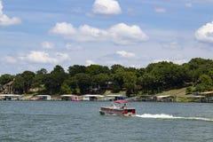 开汽车通过房子和小船船坞的浮船小船岸的在一个晴天在湖 图库摄影