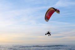 开汽车飞行在海和海滩的滑翔伞 库存照片