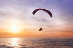 开汽车飞行在海的滑翔机在日落期间 免版税库存图片