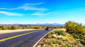 开汽车驾驶巴特利特水坝路的曲线的自行车 免版税图库摄影