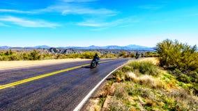 开汽车驾驶巴特利特水坝路的曲线的自行车 免版税库存图片
