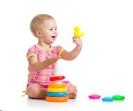 开玩笑使用与在空白背景的玩具的女孩 库存图片