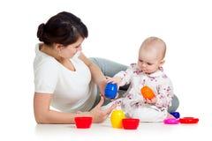 开玩笑使用与杯子玩具一起的女孩和母亲 图库摄影