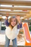 开玩笑使用在操场的女孩停止从木棒 免版税图库摄影