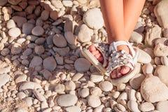 开玩笑凉鞋夏天 在石头海滩的童鞋 女孩白色时尚鞋类,皮革凉鞋,鹿皮鞋 腿  库存照片