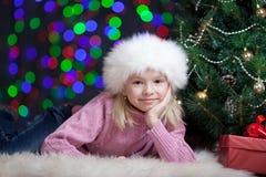 开玩笑在圣诞老人帽子打扮的女孩在x-mas结构树附近 免版税库存图片
