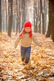 开玩笑在天鹅绒夹克、牛仔裤和红色帽子 库存图片