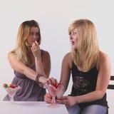 开玩笑地吃草莓的快乐的女孩 库存照片