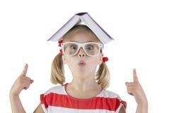 开玩笑地拿着在他的头的女小学生一本书 库存图片