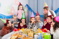 开玩笑地表现在党期间的微笑的家庭 免版税库存图片