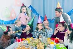 开玩笑地表现在党期间的笑的家庭 库存照片