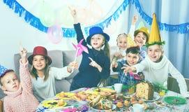 开玩笑地表现在friend's生日零件期间的男孩和女孩 免版税库存图片
