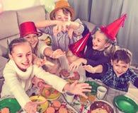 开玩笑地表现在friend's生日零件期间的男孩和女孩 库存图片