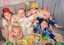 开玩笑地表现在friend's生日零件期间的男孩和女孩 免版税库存照片