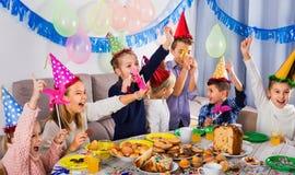 开玩笑地表现在friend's生日零件期间的男孩和女孩 免版税图库摄影