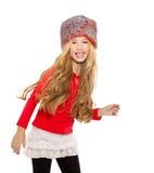 开玩笑女孩与红色衬衣和裘皮帽的冬天跳舞 免版税库存照片