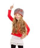 开玩笑女孩与红色衬衣和裘皮帽的冬天跳舞 免版税图库摄影