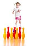 开玩笑女孩投掷的球击倒玩具保龄球栓。   免版税库存照片