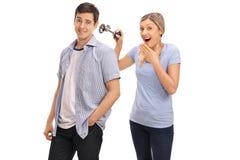 开玩笑她的男朋友的妇女通过按喇叭 库存照片