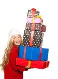 开玩笑拿着许多礼品的女孩被堆积在她的现有量 免版税图库摄影