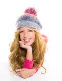开玩笑有冬天羊毛盖帽的女孩微笑在白色的 免版税库存图片