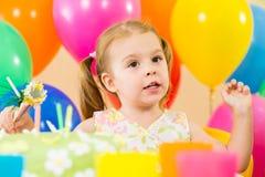 开玩笑有气球和蛋糕的女孩在生日 免版税图库摄影