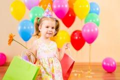 开玩笑有礼品和花的女孩在生日聚会 免版税库存照片