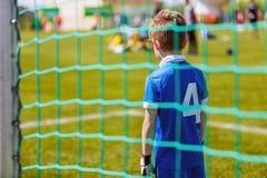 开玩笑足球比赛 作为足球守门员的年轻男孩在准备好的足球比赛期间保存 库存照片