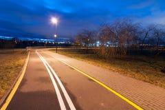 离开的城市自行车道路在秋天晚上 免版税库存照片