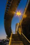 离开的步行桥在街灯照明设备的晚上  图库摄影