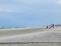 离开的海滩和有风风大浪急的海面 免版税图库摄影