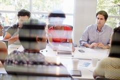 开的设计师通过窗口被观看的会议 库存照片