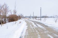 离开的结冰的被铺的道路和多云天空 库存照片