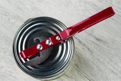 开罐头用具在锡罐 以模糊的抽象纹理为背景 图库摄影